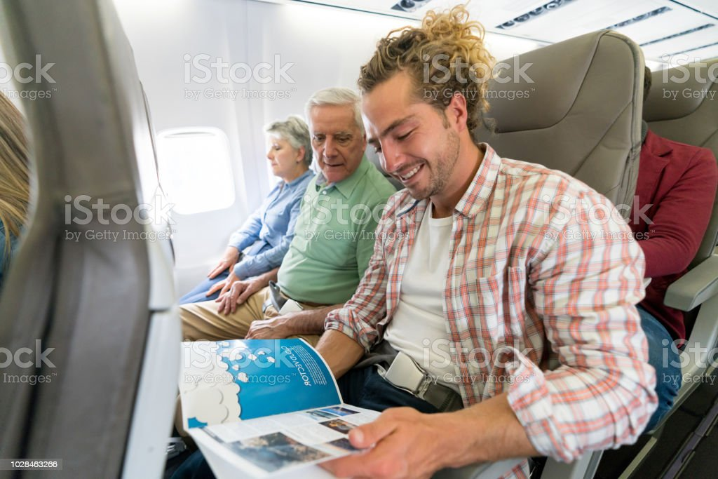 Portrait of a happy man traveling by plane and reading a travel guide...