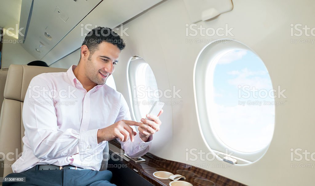 Man traveling by plane and texting on his phone stock photo