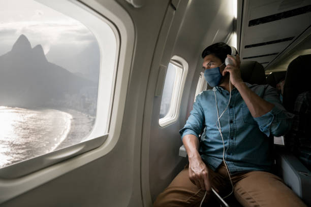 man traveling by plane wearing a facemask and looking at rio through the window - covid flight imagens e fotografias de stock