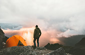 Man traveling with tent camping on mountain top outdoor adventure lifestyle  hiking active extreme summer vacations sunset and clouds view