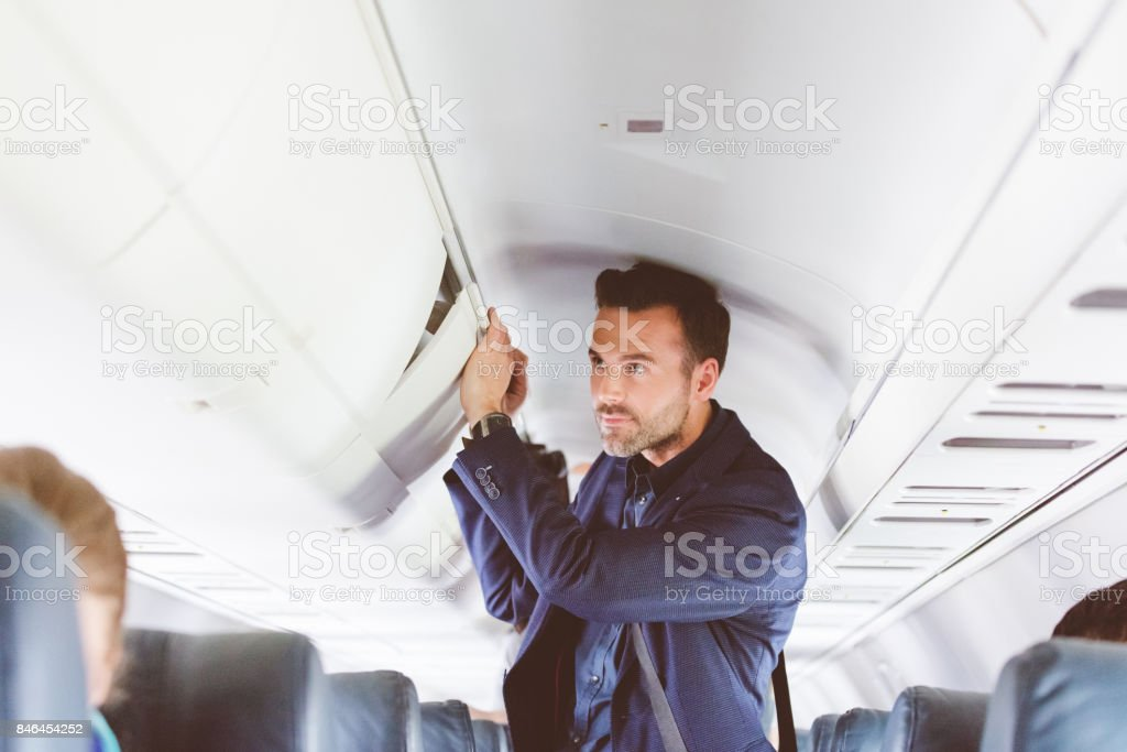 Man travelling by flight storing handbag in overhead locker stock photo