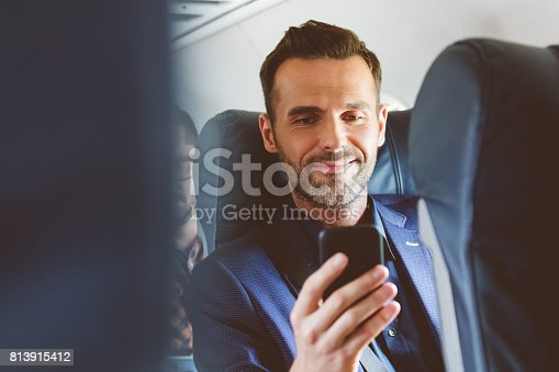 Close up of happy mature man travelling by plane and using mobile phone. Male passenger with smart phone during flight.