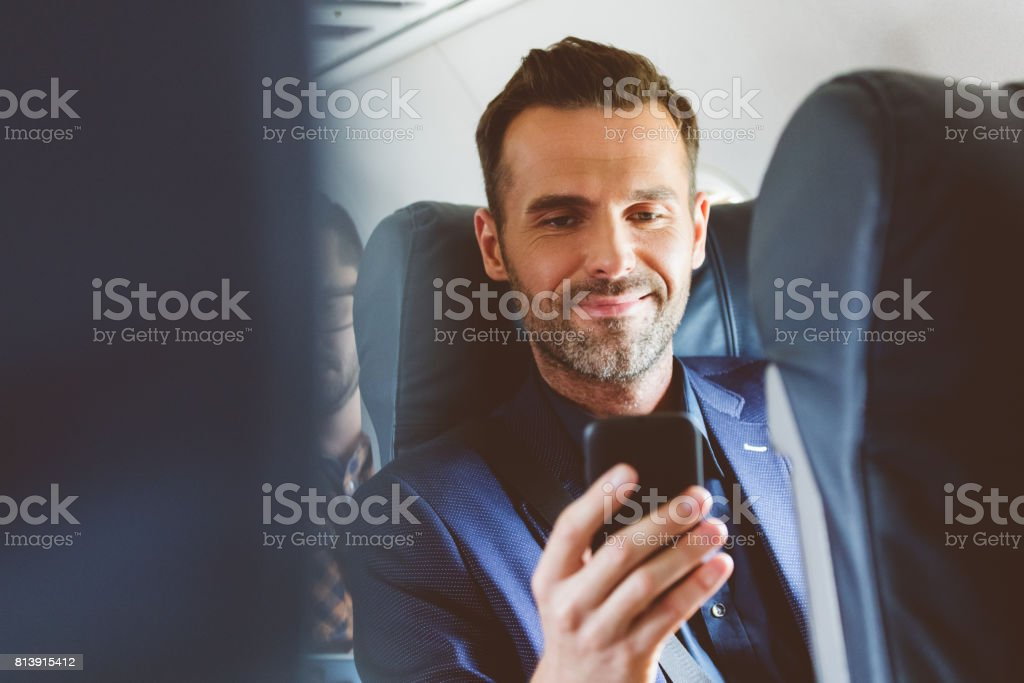 Man travelling by plane and using mobile phone stock photo