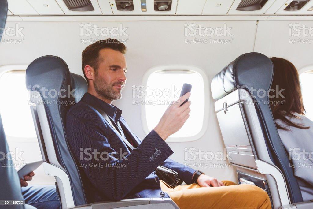 Menschen Sie reisen mit dem Flugzeug und mit Handy Lizenzfreies stock-foto