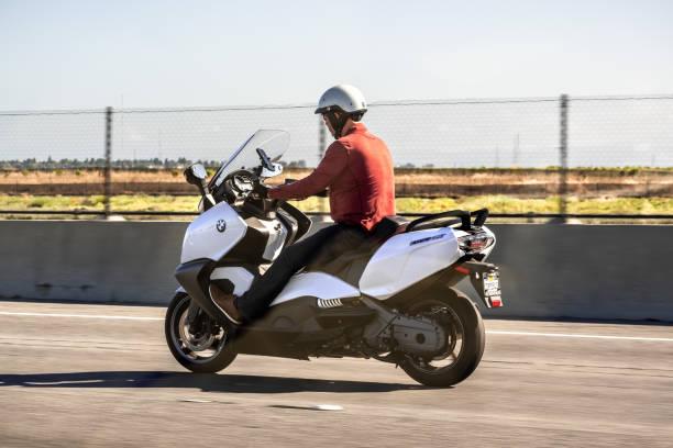 mann auf der autobahn auf einem maxi-scooter unterwegs - bmw roller stock-fotos und bilder