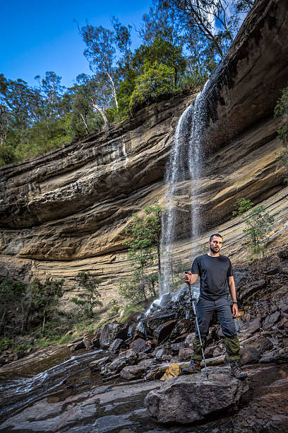Man trekking on a rocky hill with a waterfall Australia, trekking in Mount Victoria mt victoria canadian rockies stock pictures, royalty-free photos & images