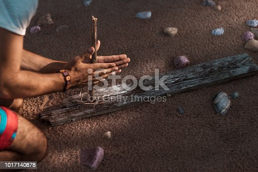 A man tries to get fire with an ancient method. A handmade bracelet on his arm. Sandy beach in the background