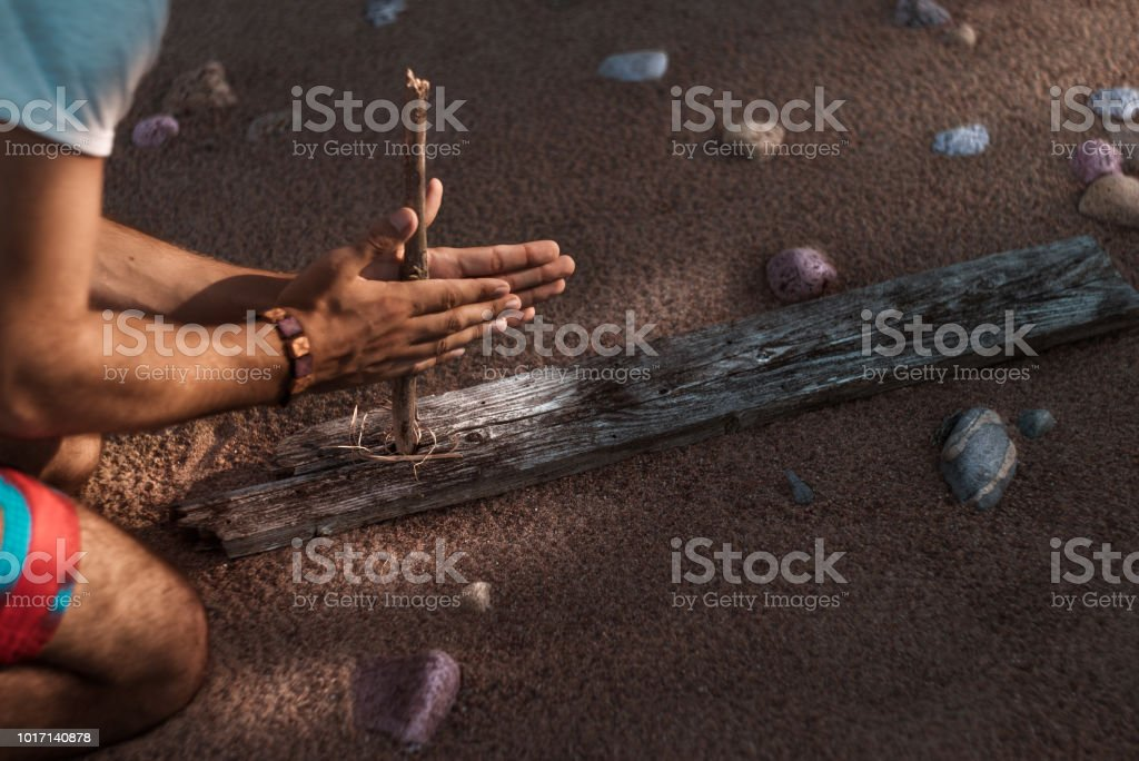 A man tries to get fire with an ancient method. Sandy beach in the background stock photo