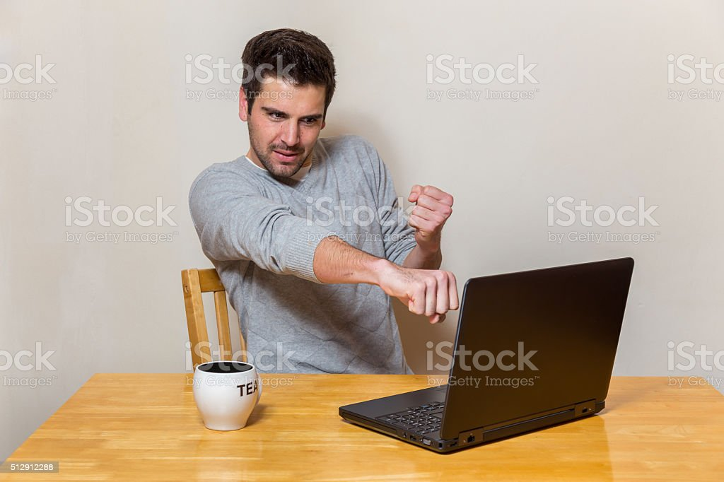 Man tries to smash the screen of his laptop stock photo