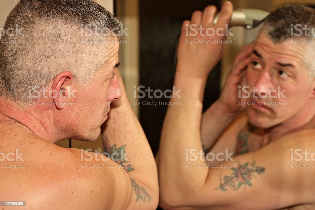 Man trimming his hair in front of the mirror royalty-free stock photo