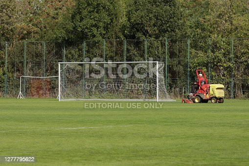 istock Man trims the turf of a stadium with a stadium grass cutter machine. 1277795622