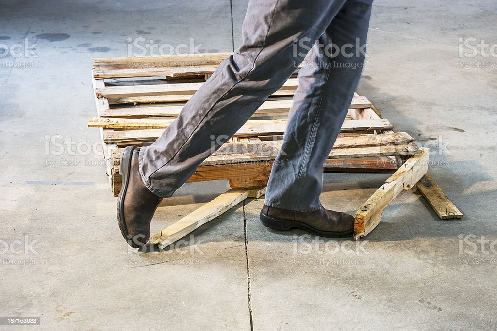 Man tripping over a damaged pallet stock photo