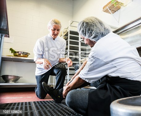 Trips, slips and falls in commercial kitchens are a major contributor to injuries sustained in the workplace.  A food service worker tripping on a curled up floor mat.  A colleague has come to his aid.