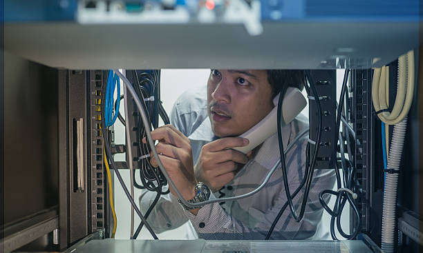 Man troubleshooting in data center with consult by telephone stock photo