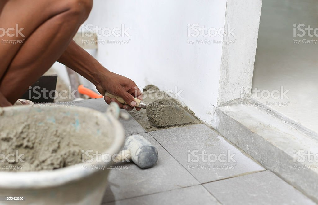 Man troweling mortar on a floor  for laying tile stock photo