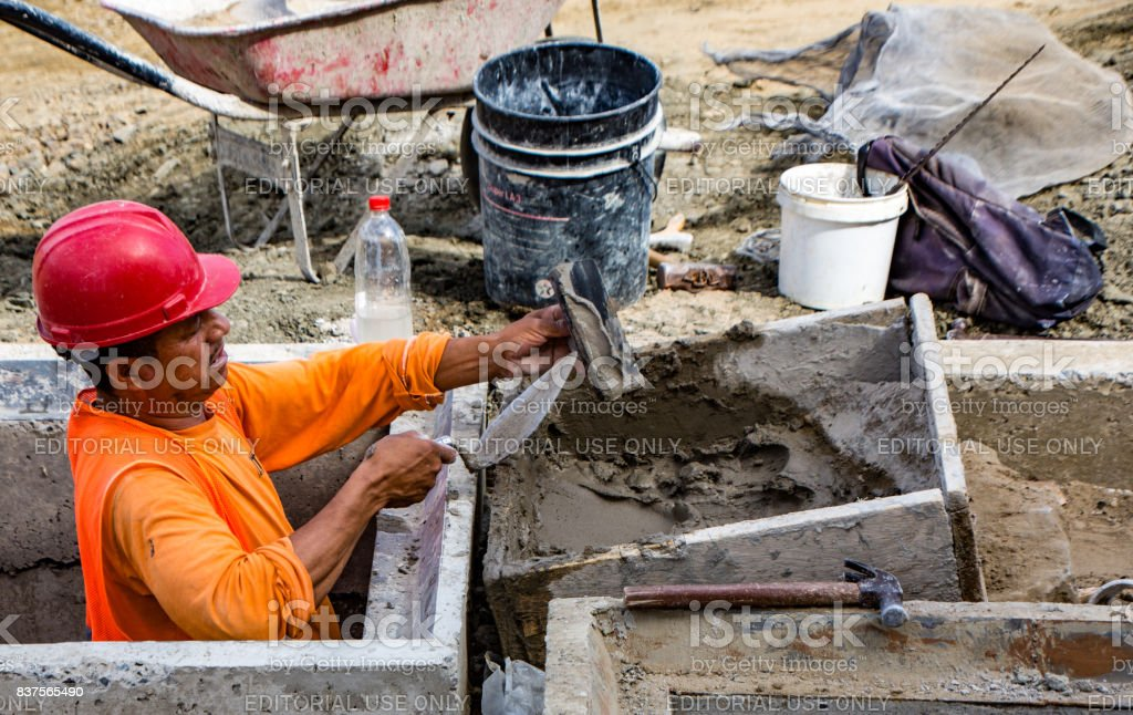 Man trowels mortor for road construction stock photo