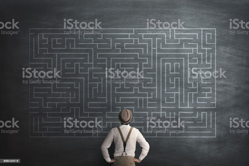 man try to solve a labyring on a chalkboard stock photo