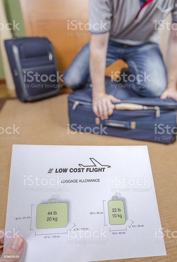 Man trying to close full hand luggage stock photo