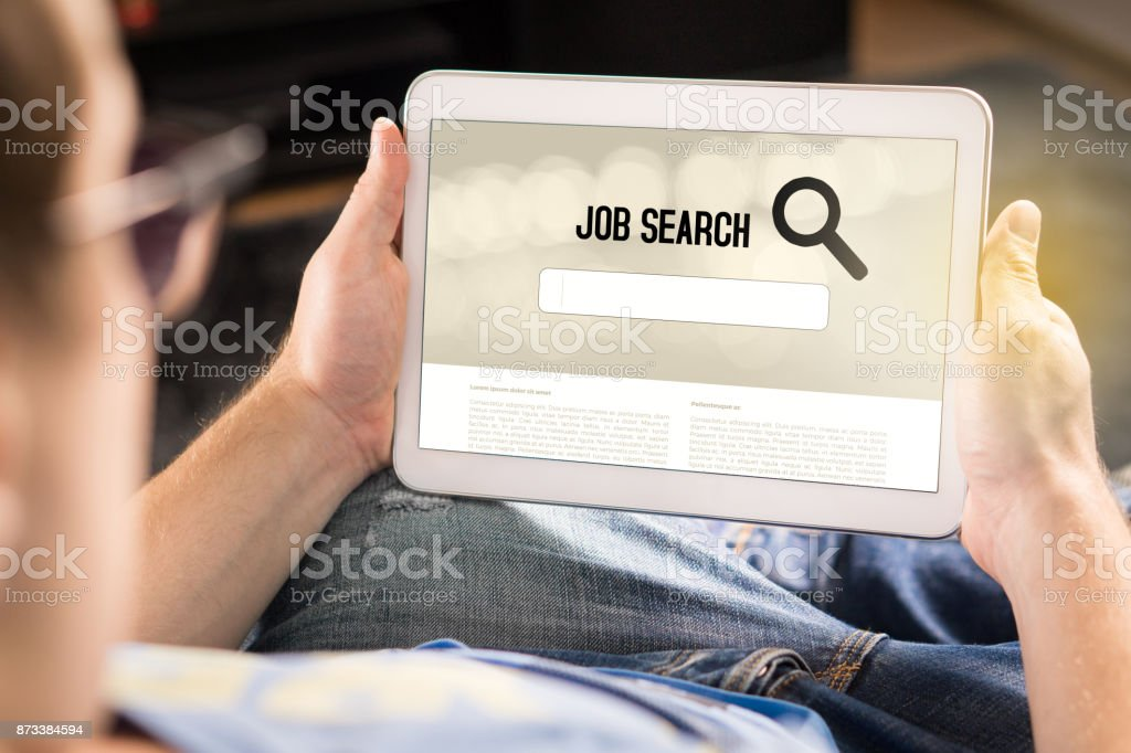 Man trying to find work with online job search engine on tablet. Jobseeker at home holding smart device. Motivated and happy applicant. stock photo