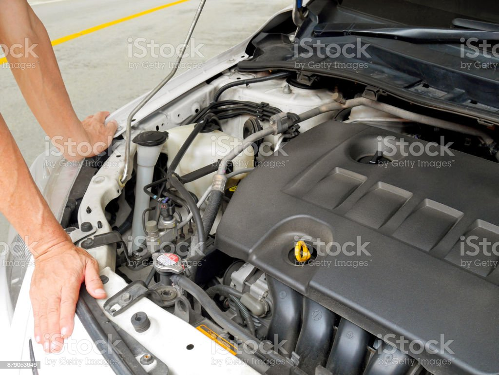 A man trying to fix broken down car stock photo