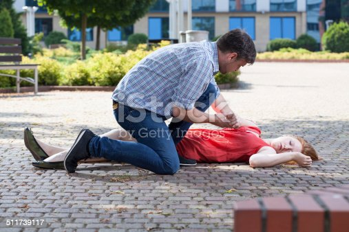 istock Man trying to help unconscious woman 511739117