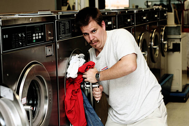 Man Trying To Load Laundry stock photo
