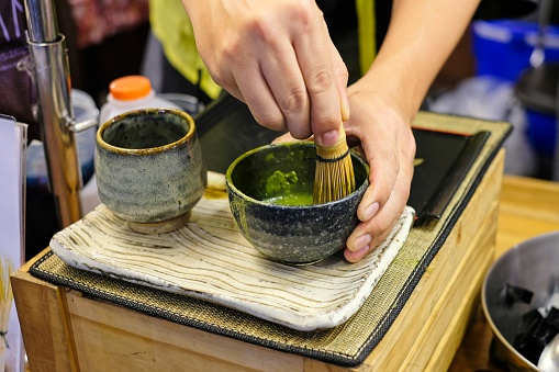 A man trying to mix a matcha green tea powder with hot water in a black bowl with a bamboo matcha whisk