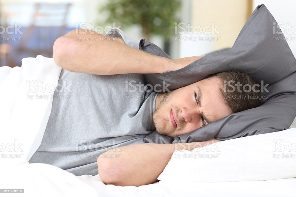 Man trying to sleep covering ears for noise stock photo