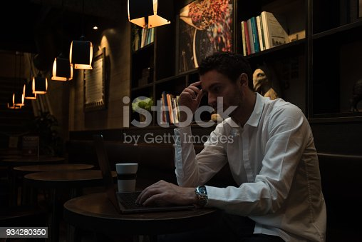 Young busy man is reading something on laptop in cafeteria.