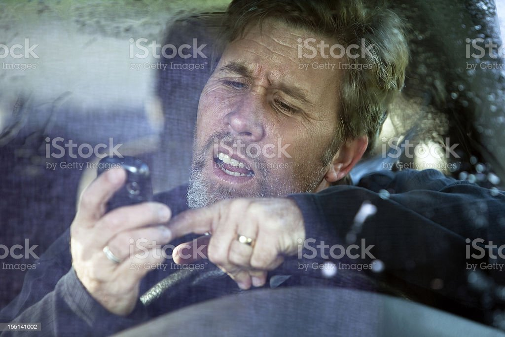 Man trying to use his phone while driving. royalty-free stock photo