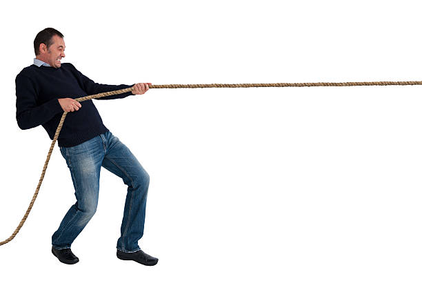 man tug of war pulling rope isolated man pulling a rope tug of war isolated white background pulling stock pictures, royalty-free photos & images