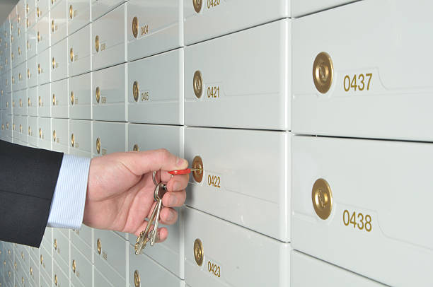 a man turning a key to a safe deposit box - depositor stock pictures, royalty-free photos & images