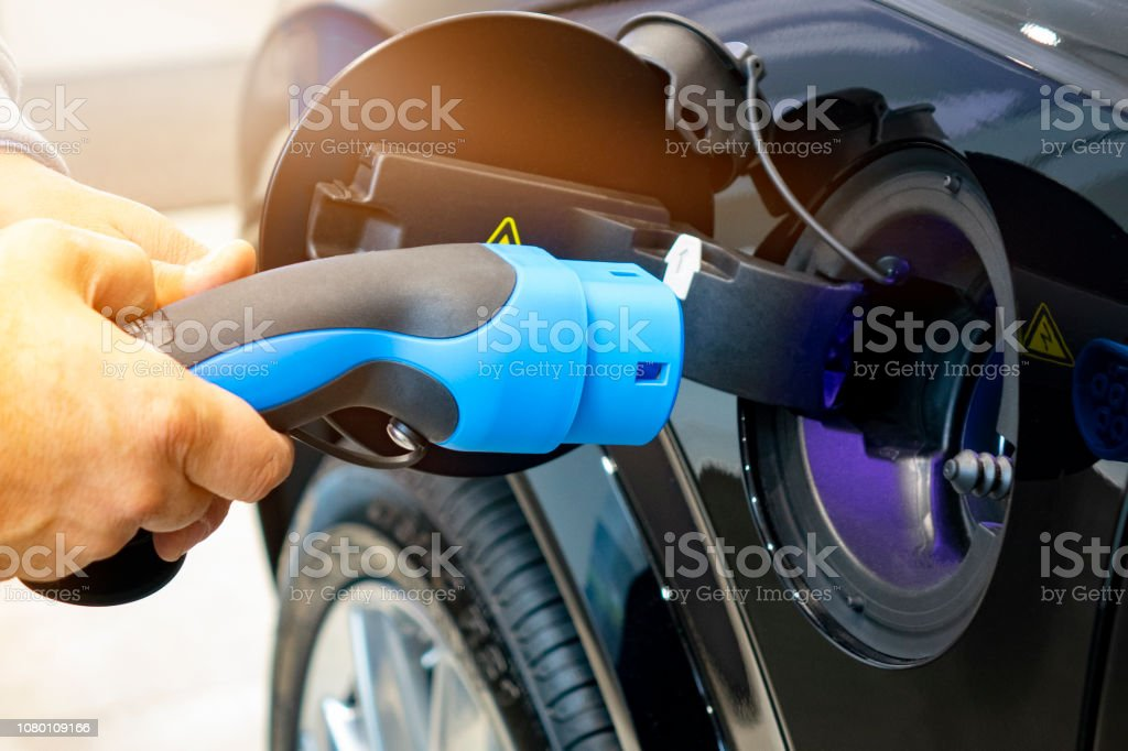 Man turning on charging of car. EV Car or Electric car at charging station with the power cable supply plugged in on blurred nature with soft light background. Eco-friendly alternative energy concept - Foto stock royalty-free di Affari finanza e industria