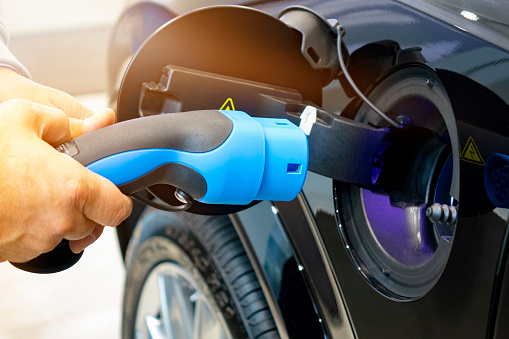 Man Turning On Charging Of Car Ev Car Or Electric Car At Charging Station With The Power Cable Supply Plugged In On Blurred Nature With Soft Light Background Ecofriendly Alternative Energy Concept - Fotografie stock e altre immagini di Affari finanza e industria