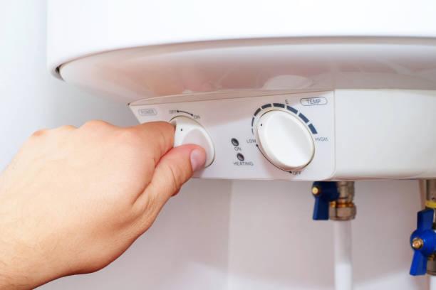 man schaltet den schalter am bedienfeld des hause elektroboiler (kessel). - heißes wasser stock-fotos und bilder