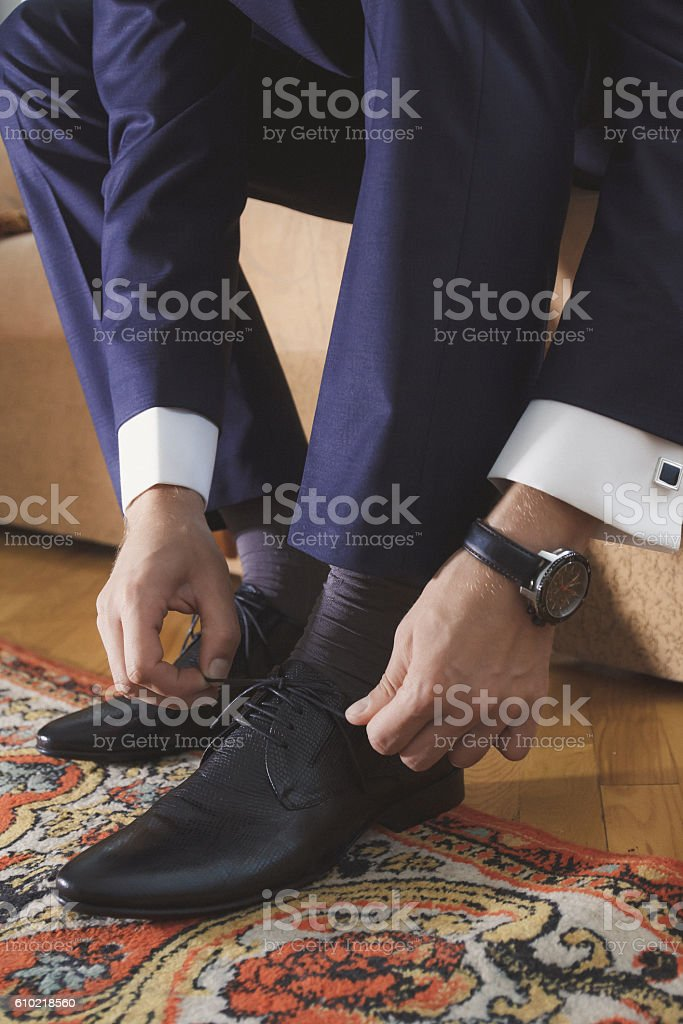 Man tying black patent leather shoes stock photo