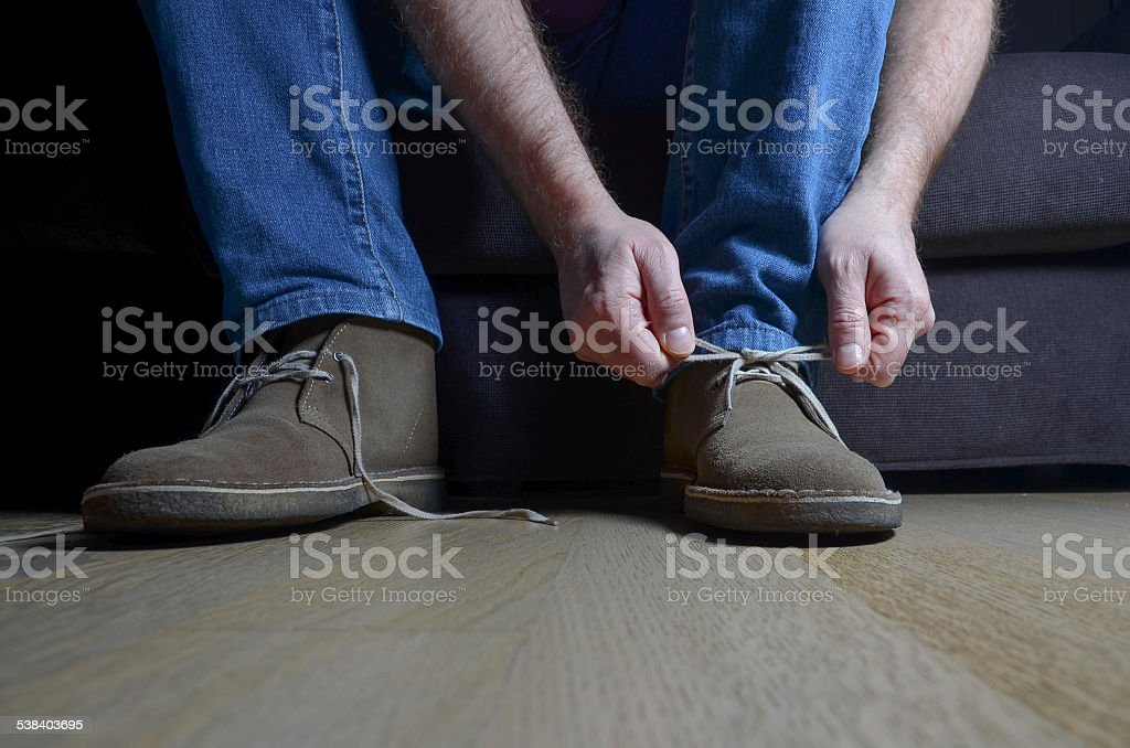 man tying casual shoes stock photo