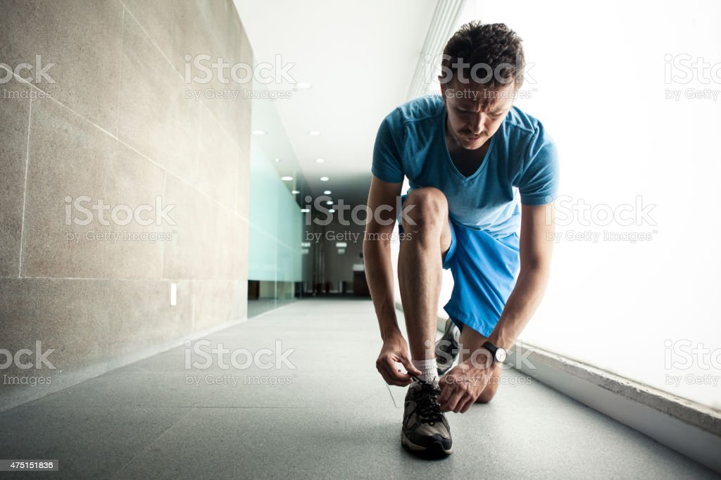 Man tying his laces before running