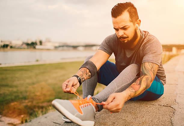 mann binden seine sports schnürsenkeln. - laufende tattoos stock-fotos und bilder