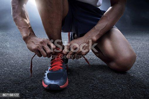 istock Man tying running shoes 807166122