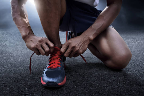 Man tying running shoes stock photo
