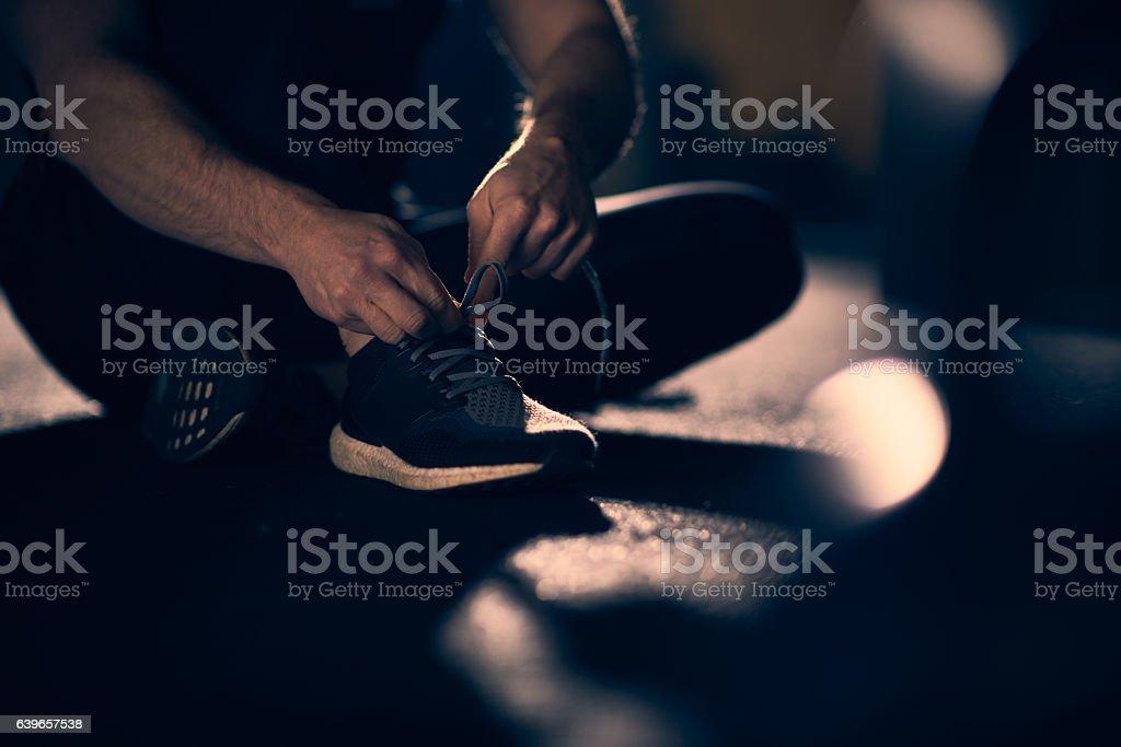 Man tying shoelaces at gym - foto de stock