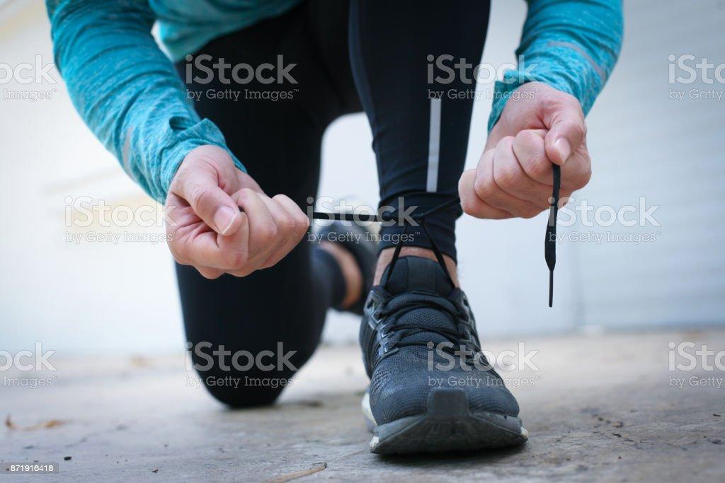 Man tying snickers before running. stock photo
