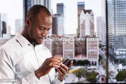 A man types a message on his smartphone against the background of panoramic windows with a view of the city
