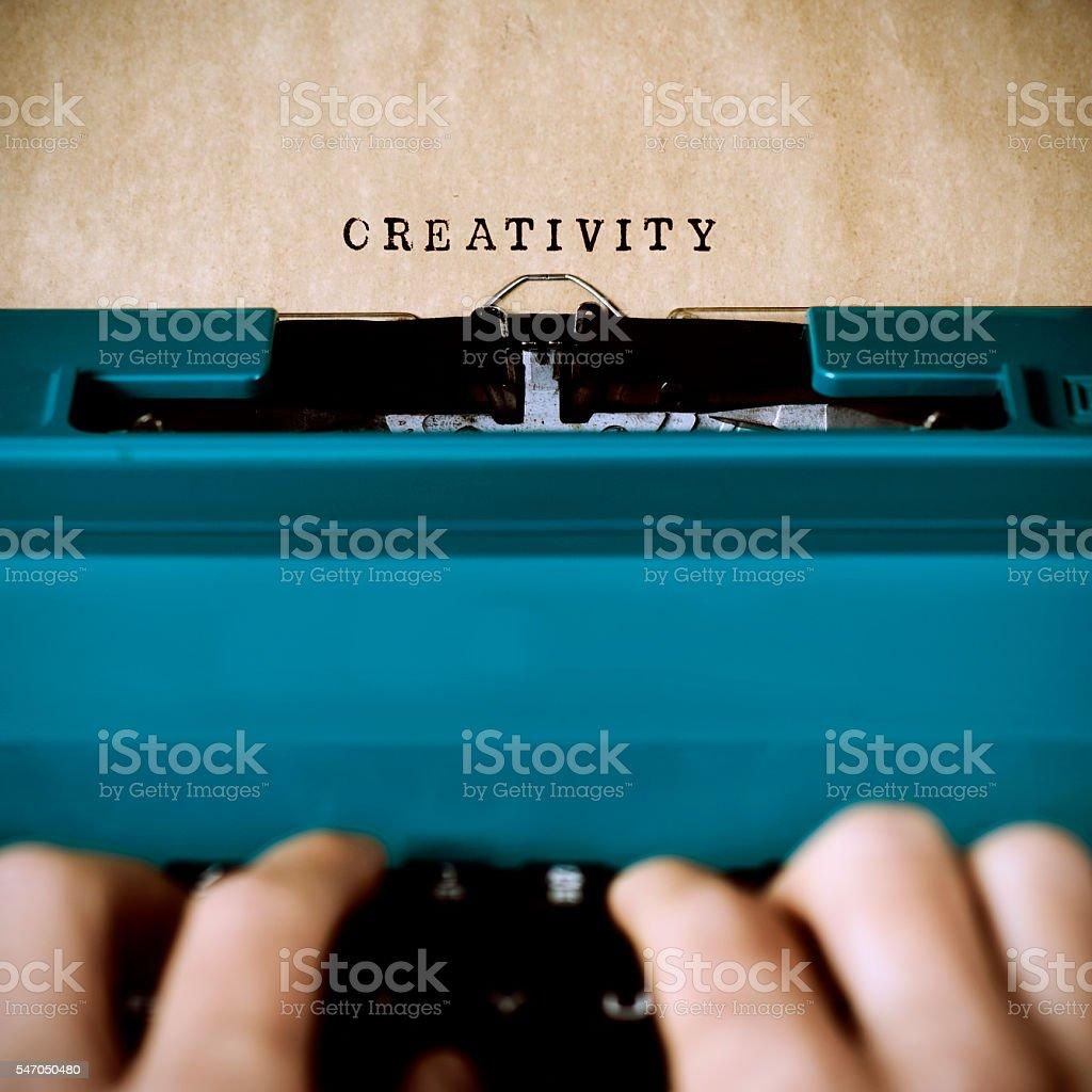 man typewriting the word creativity stock photo