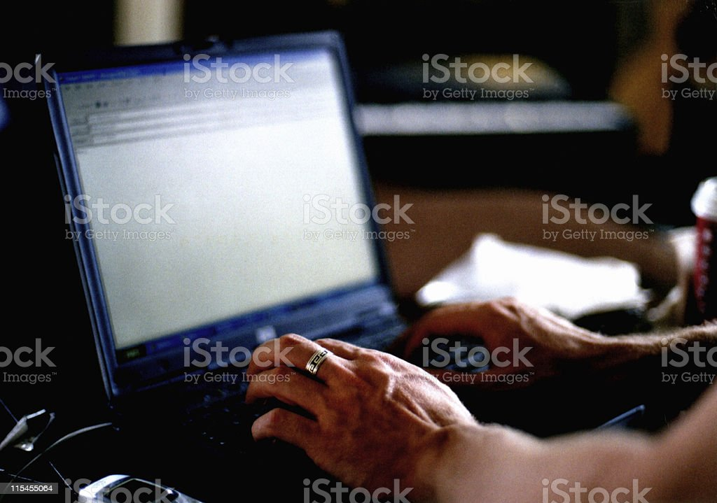 A man typing an email into a laptop stock photo