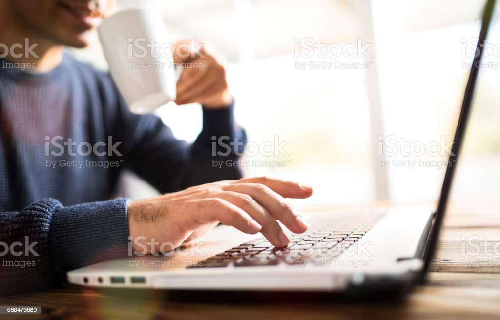 Man Typing On Computer Keyboard And Drinking Coffee stock photo