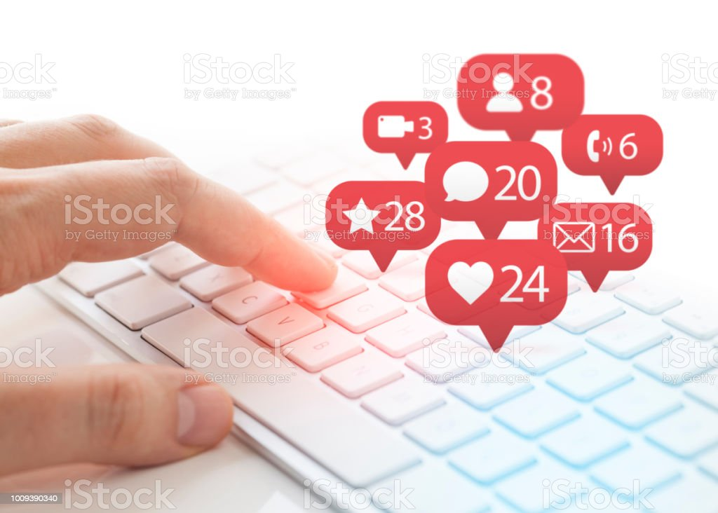 man typing on keyboard and notification icons of social network flying over keyboard stock photo