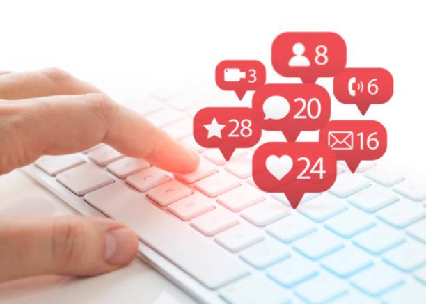 Mann, die Eingabe über Tastatur und Benachrichtigung Ikonen des sozialen Netzwerks fliegen über Tastatur – Foto