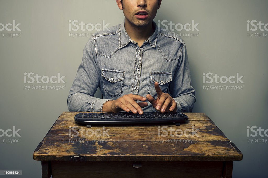 Man typing on keyboard at old desk royalty-free stock photo